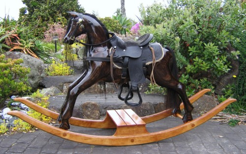 Large carved rocking horse, dark oak colour, gloss finish