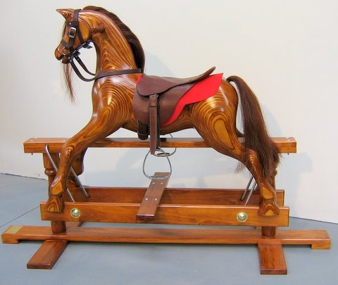 Medium oak colored rocking horse on swing stand