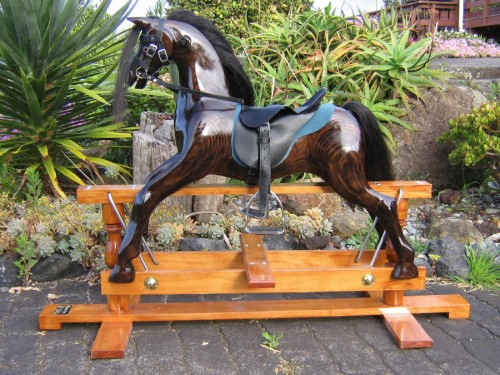 Medium rocking horse, dark oak on a stained stand